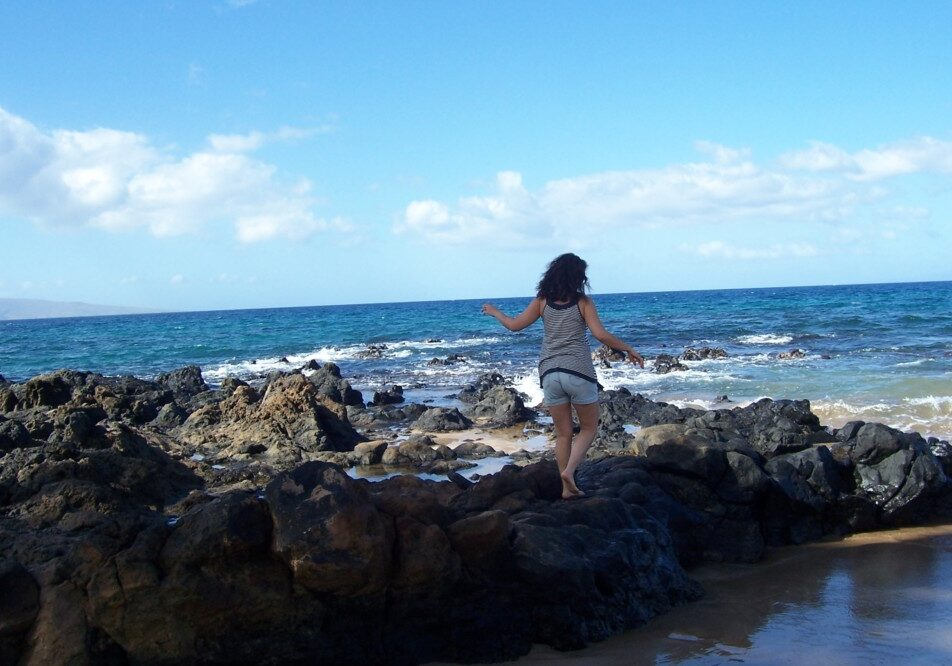 Woman walking on the rocks on the Beach in Hawaii.